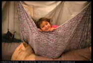 Mani, a young Innu girl plays in a tent at her family's autumn hunting camp in Labrador, Canada. Bryan and Cherry Alexander Photography.