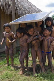 Children with body paint playing under the shade of the solar panel, used for the radio (communications). Ngoiwere Village, Mato Grosso State, Brazil. Photograph: Sue Cunningham Photographic