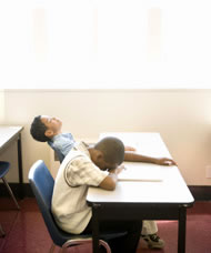 Two young students asleep at a desk in the classroom. Photograph: Blend Images/Photoshot